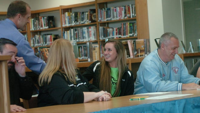 Southern Door softball player Acacia Tupa signs a scholarship offer to play softball at the University of Wisconsin-Green Bay. Tupa is the first Southern Door softball player to win a scholarship to an NCAA Division 1 school. HShaking Tupa's hand is school principal Steve Bousley, and joining her are her parents, Dave and Sharon, left, and Eagles softball coach Pat Delcore.