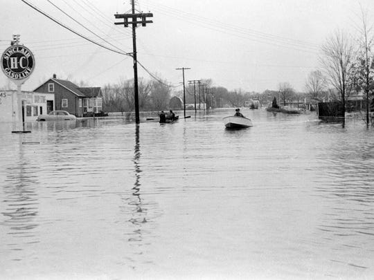 A police officer uses a motorboat to travel south on Route 13, Meadow Street, after a flood in Ithaca during spring 1956. This flood, and a devastating flood in 1935, provoked the U.S. Army Corps of Engineers to build Ithaca's flood control channel.