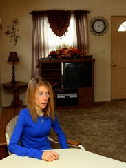 Allison Rademacher sits in her living room at her house
