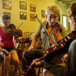 Jonno Frishberg, second from right, teaches a group of campers fiddle technique during Louisiana Folk Roots' Kids Camp at Vermilionville in Lafayette Thursday.