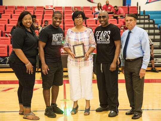 "Sandra Floyd, the widow of Lt. Steven Floyd, who was killed during the prison uprising at the James T. Vaughn Correctional Center near Smyrna on Feb. 1, receives a plaque on behalf of her daughter Chyvante Floyd, a Delaware State University student, during the ""Justice for All"" basketball tournament on April 29 at DSU. From left are: Kayla Smith (DSU Housing staff), Robert Price (resident director at DSU's University Village Apartments), Sandra Floyd, Donnell Fears (Fears Promotions) and Robin Christiansen (Dover mayor)."