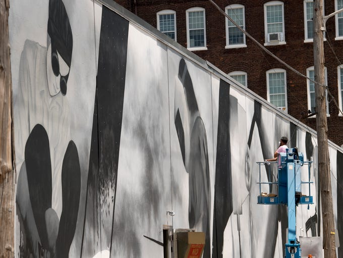 Jayemaich, the mural artist, works on a partially completed