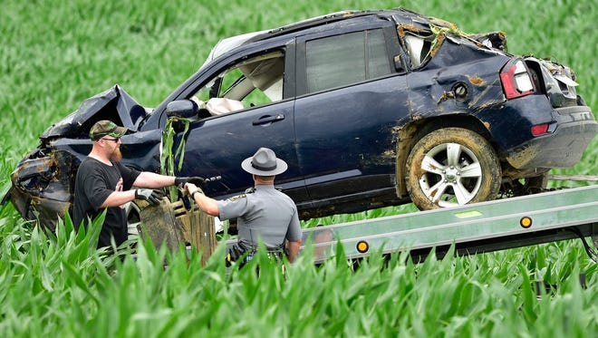 A state police trooper watches as a tow truck driver prepares to haul a late model Jeep Compass from a farmer's field Thursday, June 23, 2016 at Rice Road, Shippensburg. Two people were reportedly injured during the rollover crash.