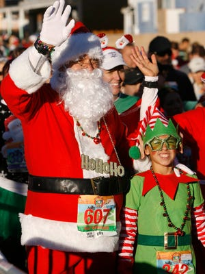 Dressed as Santa Claus and an elf, Lucio Diaz (left) and Angelina Apodaca, both of Camarillo, start the Santa to the Sea half marathon in Oxnard last year.