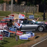 Campaign supporters stand in a sea of signs outside the voting precinct located at Victory Baptist Church in Madison Tuesday morning.