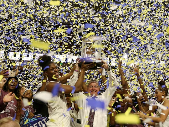 Mississippi State head coach Vic Schaefer and Teaira McCowan raise the Tournament trophy after winning an NCAA college basketball championship game against Arkansas in the Southeastern Conference women's tournament, Sunday, March 10, 2019, in Greenville, S.C. (AP Photo/Richard Shiro)