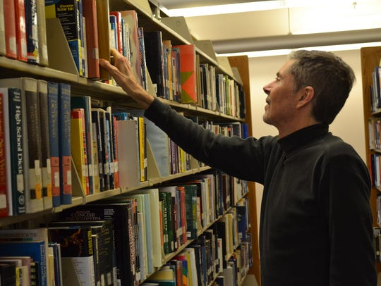 Tom Adamich stacks books in the library of Terra State