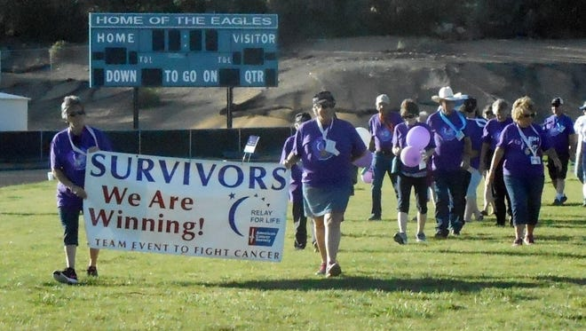 Cancer survivors walk across the football field Saturday during the Relay for Life at Navajo Preparatory School in Farmington.