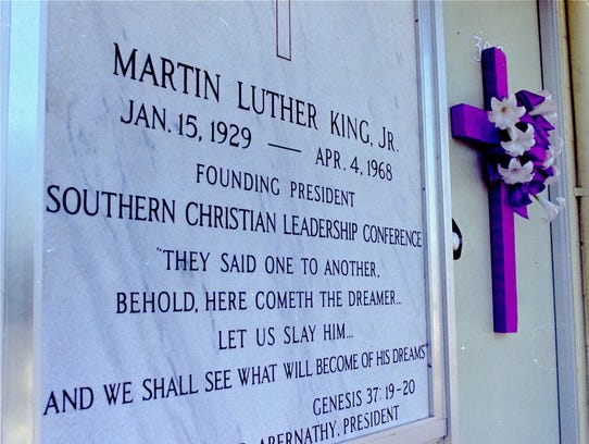 A  memorial plaque and cross on the exterior of Room