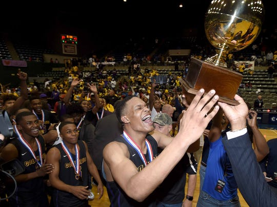 The Columbus Falcons and Robert Woodard celebrate with the Class 6A trophy after beating Meridian in the finals of the MHSAA C Spire State Basketball Tournament at the Mississippi Coliseum in Jackson, Miss., on Saturday, March 10, 2018.