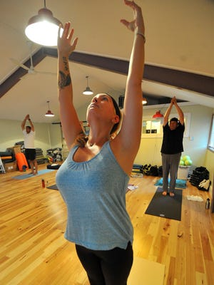 Casey Nick, of Wausau, practices yoga with a group at Croi Croga Studio in Wausau last month.
