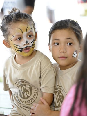 Two girls with painted faces watch as another gets her face painting done during the Sanctuary Inc.'s Youth Fest 2014 at Agat Sagan Bisita on April 5.