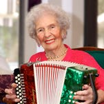 Grace Littlefield plays accordion for a crowd in the dining room with Berna Austin and Wesley Rymer (of Berna and the Bernouts) at The Health Center of Merritt Island, where 102-year-old Littlefield is a resident.