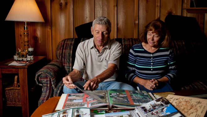 Al and Fay Frost look over photo albums from their travels, in their living room at their North Street home.