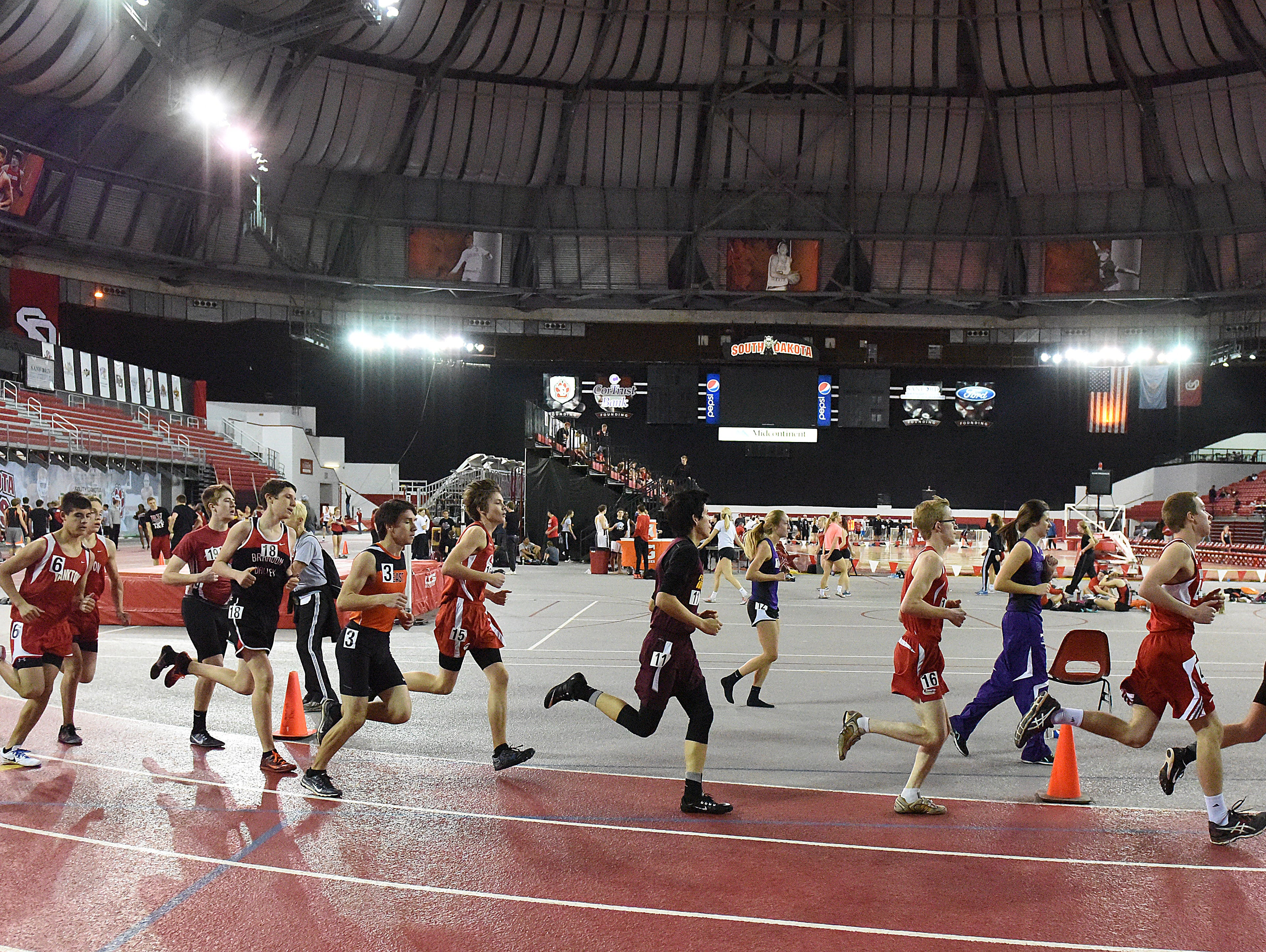 Runners make their way around the track in the boys 1600 meter run during the Dan Lennon Invitational at the DakotaDome in Vermillion on Monday, March 28, 2016.
