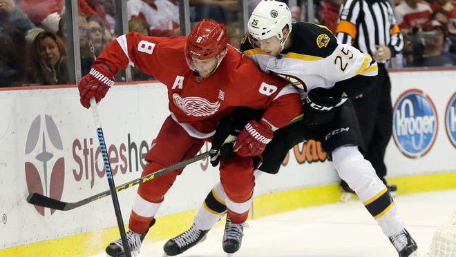 Red Wings left wing Justin Abdelkader (8) tries to maintain control of the puck against Bruins defenseman Brandon Carlo (25) during the second period Saturday at Joe Louis Arena.