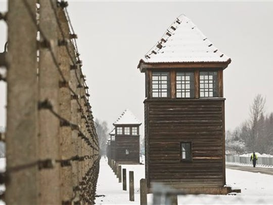 Barbed wire fences and guard towers surround the access road into the Birkenau Nazi death camp in Oswiecim, Poland, on Jan. 26, 2015. A decade ago, 1,500 Holocaust survivors traveled to Auschwitz to mark the 60th anniversary of the death camp's liberation.