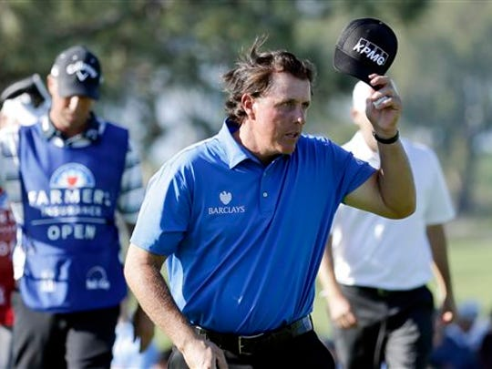 Phil Mickelson, right, tips his hat after finishing