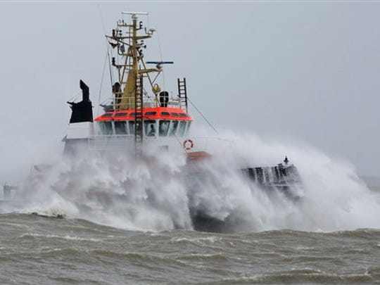 Waves created by strong winds swamp a towboat  on the