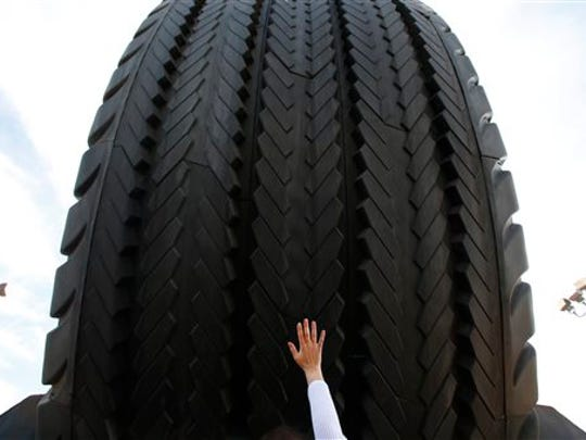 A visitor reaches for the Giant Uniroyal Tire, Wednesday, May 20, 2015, in Allen Park.