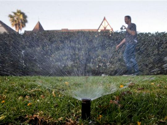 Tony Corcoran records sprinklers watering the lawn June 5, 2015, in front of a house in Beverly Hills, Calif. Corcoran is one of several people who spend their spare time these days canvassing California communities  looking for people wasting water during the worst California drought in recent memory.