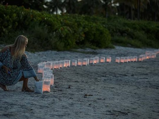 Lilly Folds lights paper lanterns during a candlelight vigil and paper balloon release at Jupiter Inlet Park, Monday, July 27, 2015, for teenagers Austin Stephanos and Perry Cohen in Jupiter, Fla. The teens were last seen Friday afternoon buying fuel near Jupiter and were believed to have been heading toward the Bahamas.