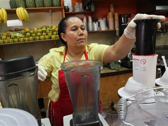 Celina Alvarez, 51, works at Jugueria de regreso al Eden, her shop in the Queens borough of New York, Monday Aug. 3, 2015. As a campaign to raise the minimum wage as high as $15 has rolled to victory in such places as Seattle, Los Angeles and New York, it has bumped up against a harsh reality: Plenty of scofflaw businesses don't pay the legal minimum now and probably won't pay the new, higher wages either.
