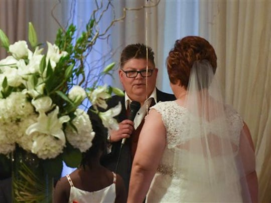Jayne Rowse, left, says her vows to April DeBoer, during a marriage ceremony in Southfield, Mich., Saturday, Aug. 22, 2015. The two Michigan women legally challenged the state's ban on gay marriage and Federal Judge Bernard Friedman, who overturned the state's ban in 2014, performed their wedding.