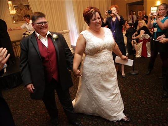 Jayne Rowse, left, and April DeBoer, right, legally marry at a banquet hall in Southfield, Mich. on Saturday, Aug. 22, 2015. The US Supreme Court struck down bans on same-sex marriage nation wide on Friday, June 26, 2015. A judge who overturned Michigan's ban on gay marriage says he's willing to officiate at the marriage of two Hazel Park nurses at the center of the groundbreaking case.