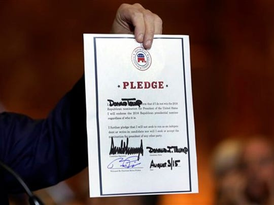 Republican presidential candidate Donald Trump holds a signed a Republican loyalty pledge to back the Republican's 2016 nominee for president and skip a potential third-party bid, at Trump Tower, in New York,  Thursday, Sept. 3, 2015.