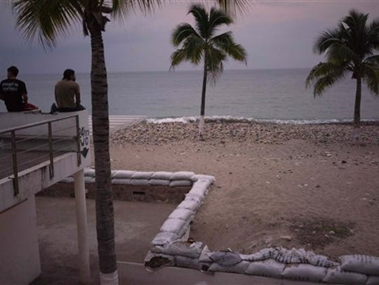 Two men sit out by the beach as hurricane Patricia