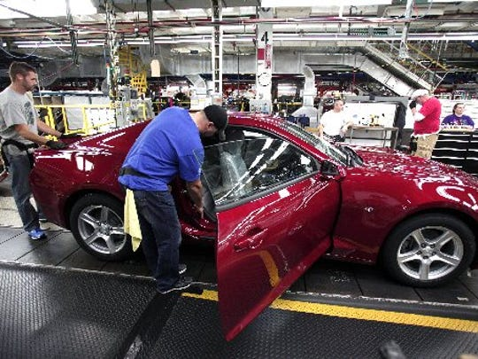Workers put the finishing touches on a 2016 Chevrolet Camaro as it rolls off the assembly line at the Lansing Grand River plant.