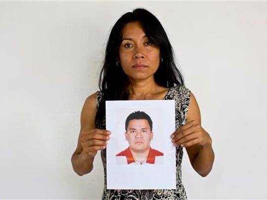 Adriana Bahena Cruz sostiene una fotografía de su esposo,