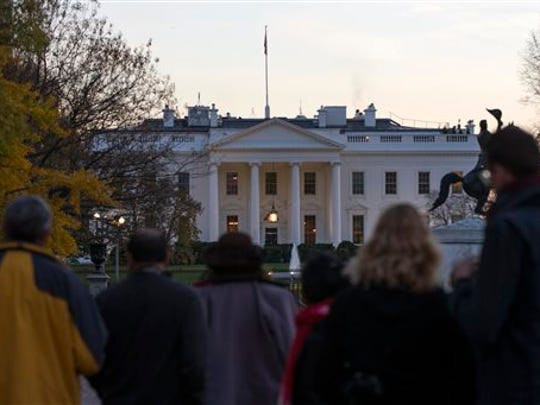 People gather outside the White House after the Secret Service arrested a man who was caught jumping the fence as President Barack Obama and his family ate Thanksgiving dinner, on Thursday, Nov. 26, 2015, in Washington.