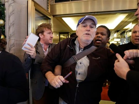 Associated Press reporters Warren Levinson, center, and Jake Pearson, left, are ejected from the lobby of The Plaza Hotel in New York, where Republican presidential candidate Donald Trump was attending the Pennsylvania Republican party's annual Commonwealth Club luncheon, which was closed to the press, on Friday, Dec. 11, 2015. Protesters who disrupted the event were also removed from the hotel.
