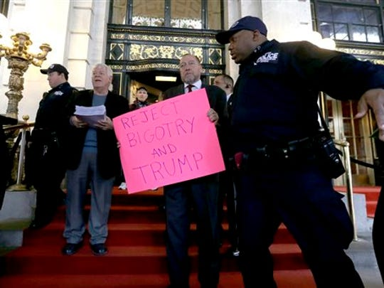 Activists trying to deliver a petition are barred from entering The Plaza Hotel, where Republican presidential candidate Donald Trump is attending the Pennsylvania Republican party's annual Commonwealth Club luncheon, Friday, Dec. 11, 2015, in New York.