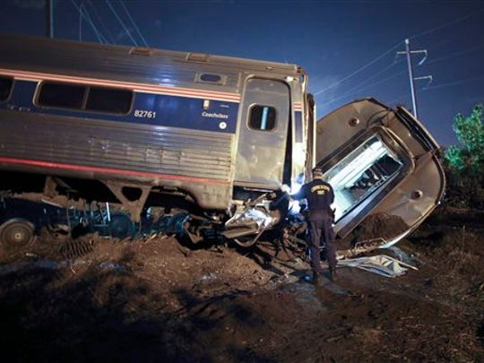 FILE - In this May 12, 2015, file photo, emergency personnel work the scene of a deadly train wreck in Philadelphia. An Amtrak train headed to New York City derailed and crashed in Philadelphia. Federal authorities continue to investigate the crash that killed eight people and injured more than 200. The train derailed while traveling more than twice the speed limit around a curve; travel along the Northeast Corridor was disrupted for days while the tracks were replaced.