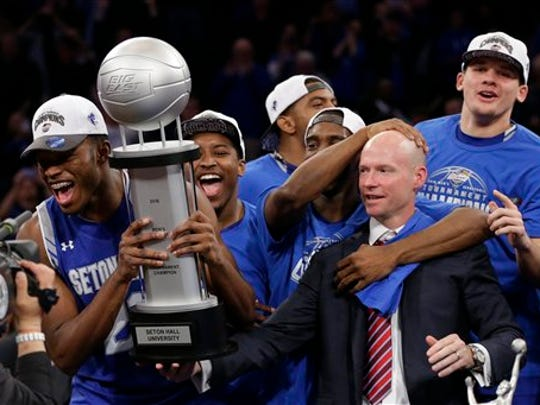 Seton Hall head coach Kevin Willard, right, watches the Pirates celebrate the Big East Tournament title.