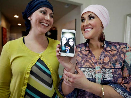 In this Thursday, May 26, 2016, photo, Annette Page, left, and her sister Sharee Page, hold a cell phone with a photograph of the two of them before being diagnosed with cancer during an interview, in Farmington, Utah.