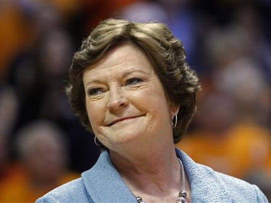 The late, former Tennessee women's basketball coach Pat Summitt smiles as a banner is raised in her honor before the team's NCAA college basketball game against Notre Dame in Knoxville on Jan. 28, 2013.