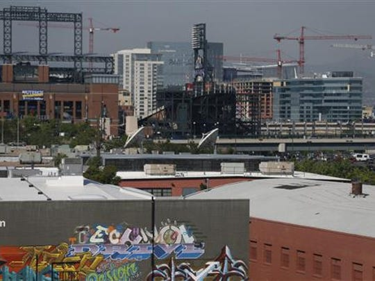 """In this June 29, 2016 photo, cranes dot the landscape in downtown Denver. Richard Florida, a prominent urban theorist, argues that living in a booming city, with its high cost of living, can be tougher than living in a slowly depopulating rural area. """"People in urban and rural areas are living very different lives and experiencing the world very differently,"""" Florida said."""
