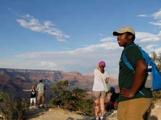 Grand Canyon National Park intern Mi-Kal White looks waits for visitors to approach him for assistance on July 26, 2016. As the National Park Service prepares to celebrate its 100th anniversary on Aug. 25, the agency is working to attract more minorities to the country's national parks and monuments as the demographics of America are expected to change dramatically in the coming years. (AP Photo/Beatriz Costa-Lima)