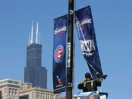 Brian Terry, of Bannerville USA, installs 2016 World Series Champions, Chicago Cubs banners as preparations for the parade and rally to celebrate the Cubs World series victory are rolled out along south Columbus Dr. in Chicago's Grant Park, Thursday, Nov. 3, 2016.