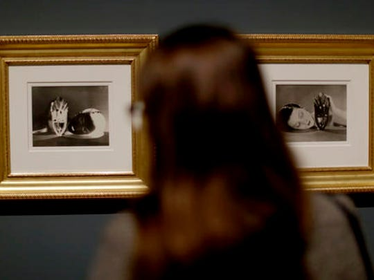 A woman looks at positive and negative prints of Man
