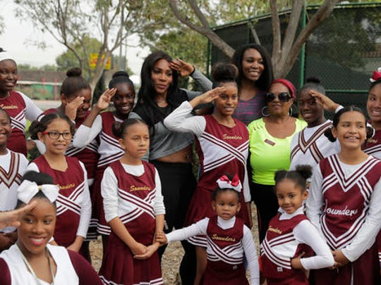 Serena Williams, center left, and sister, Venus, pose with the members of the Compton Sounders drill team after attending a dedication ceremony of the Lueders Park tennis courts Saturday, Nov. 12, 2016, in Compton, Calif. The courts were dedicated in their name.