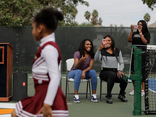 CORRECTS PARK SPELLING TO LUEDERS, NOT LEUDERS - Venus Williams, second from left, and sister Serena watch a performance by the Compton Sounders drill team during a dedication ceremony of the Lueders Park tennis courts Saturday, Nov. 12, 2016, in Compton, Calif. The courts were dedicated in their name.
