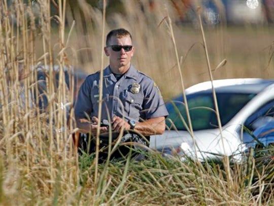 An Oklahoma City police officer looks through tall