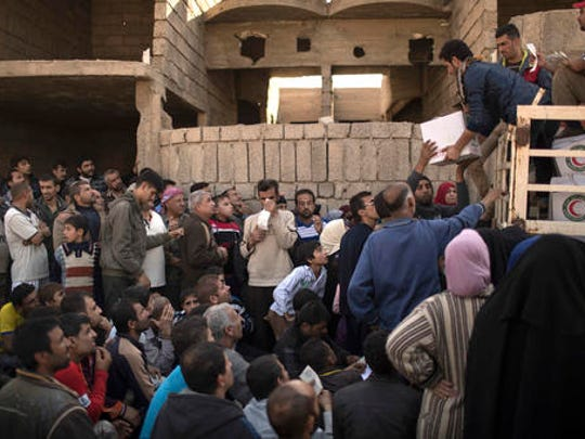 Residents gather to receive food supplies being distributed in an area previously held by Islamic State militants and now controlled by Iraqi forces in Mosul, Iraq, Thursday, Nov. 17, 2016.