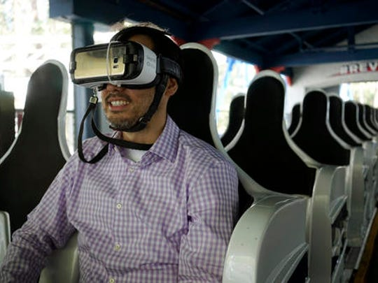 In this June 27, 2016, photo, Associated Press business writer Ryan Nakashima prepares to ride The New Revolution, a virtual reality roller coaster at Six Flags Magic Mountain in Valencia, Calif. People who are curious about virtual reality but don't want to plunk down $1,000 or more on hardware are increasingly getting the chance to test out the medium for a price. From roller coaster rides to baseball games, VR can bring a new level of reality or simply detract from it.