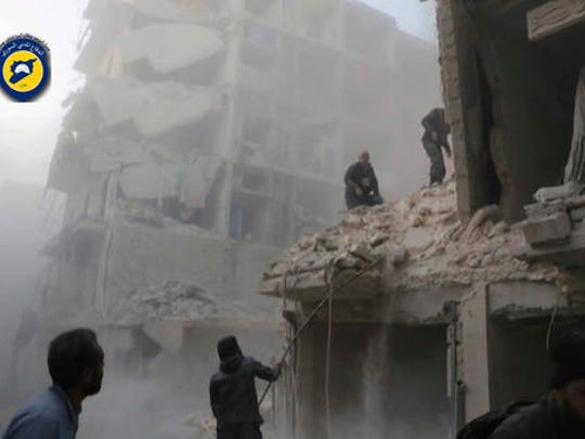 This photo provided by the Syrian Civil Defense White Helmets, which has been authenticated based on its contents and other AP reporting, shows Syrian citizens inspect damage buildings after airstrikes hit the Seif al-Dawleh neighborhood in Aleppo, Syria, Saturday, Nov. 19, 2016. Government bombardment of besieged rebel-held neighborhoods in the northern city of Aleppo killed at least 20 people Saturday Syrian opposition activists said, a day after the health directorate said all hospital in opposition areas have been knocked out of service.